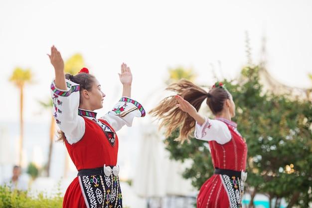 Il gruppo olklore vestito con abiti tradizionali sta eseguendo danze nazionali bulgare.
