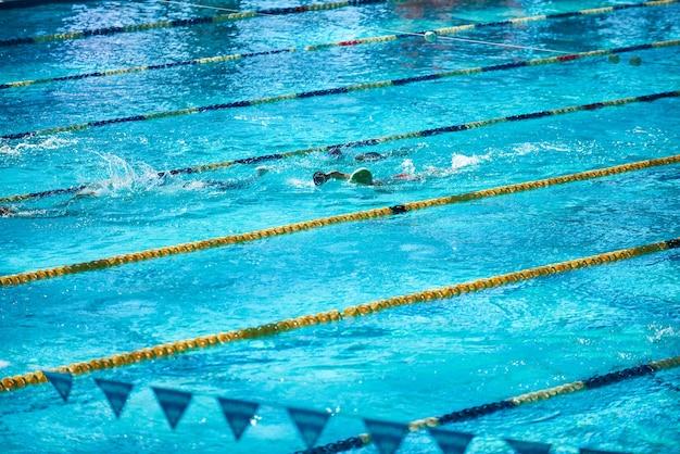 Grande piscina sportiva olimpionica con persone irriconoscibili che nuotano nell'acqua.