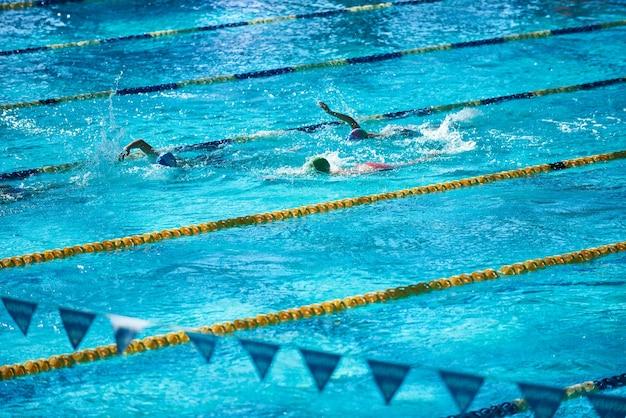 Piscina sportiva olimpionica con persone irriconoscibili che nuotano nell'acqua.