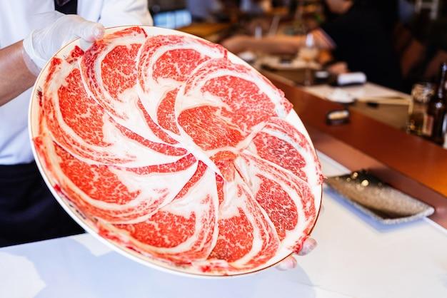 Omakase chef presenta rare fette di carne di manzo wagyu kagoshima con una consistenza marmorizzata su un piatto circolare