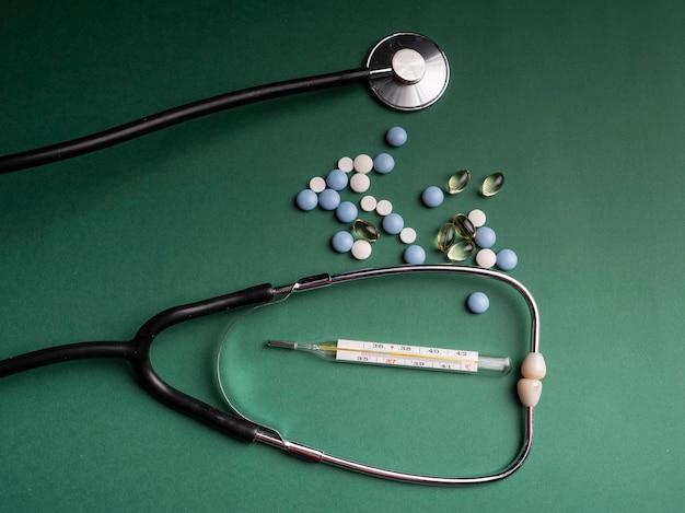 Capsule di omega 3, uno stetoscopio in cui giace un termometro e varie pillole mediche