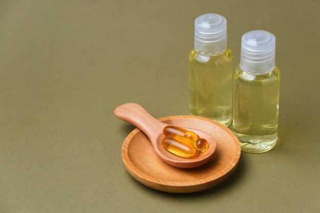Capsule di omega 3 nel cucchiaio di legno e due bottiglie di plastica di oli su sfondo verde oliva