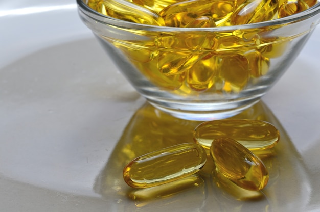 Capsule di olio di pesce omega-3 e vitamina d in una lastra di vetro.