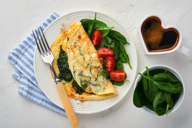Frittata o frittata con condimento di spinaci, pomodorini e pepe su piatto bianco