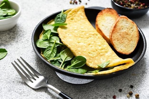 Frittata con spinaci per colazione in padella di ghisa su fondo in cemento.