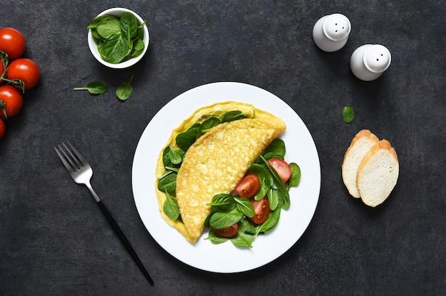 Frittata con spinaci per colazione in un piatto su uno sfondo nero di cemento.