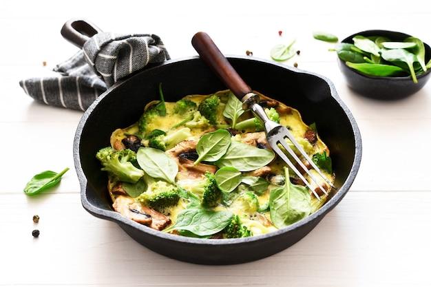 Frittata con spinaci e funghi in padella di ghisa su fondo in legno chiaro. fritata con spinaci.
