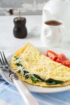 Frittata con spinaci, prezzemolo e formaggio per colazione su una superficie leggera