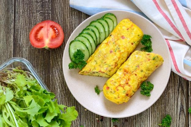 Frittata, involtino con verdure ed erbe su un tavolo di legno. deliziosa colazione salutare. vista dall'alto.