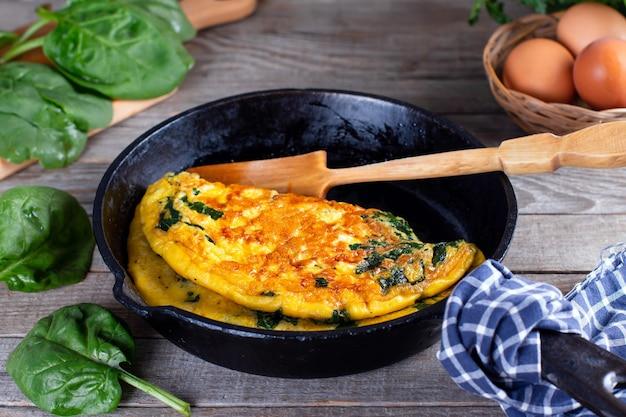 Frittata ripiena di spinaci e formaggio per una colazione. frittata con foglie di spinaci.