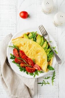 Frittata con avocado, pomodori e rucola sul piatto in ceramica bianca su sfondo di pietra chiara