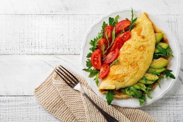 Frittata con avocado, pomodori e rucola sul piatto in ceramica bianca sulla superficie della pietra chiara. colazione salutare. messa a fuoco selettiva. vista dall'alto.