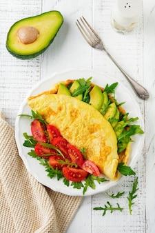 Frittata con avocado, pomodori e rucola sul piatto in ceramica bianca sulla superficie della pietra chiara