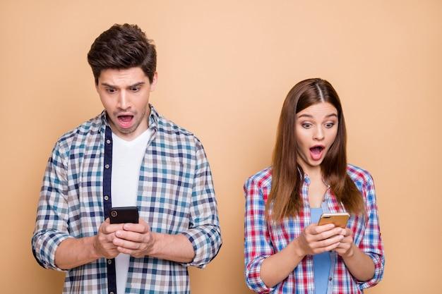 Oh mio dio! ritratto di blogger di coniugi colpiti utilizza lo smartphone che naviga per ottenere notifiche sui social network sentirsi stupore guardare in abito casual plaid di usura dello schermo isolato su sfondo di colore pastello