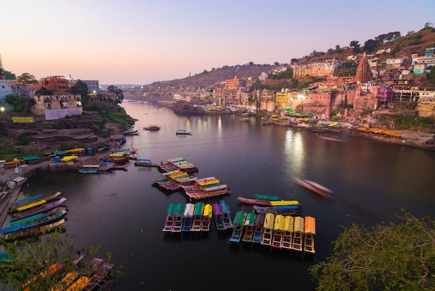Paesaggio urbano di omkareshwar al crepuscolo, india, tempio indù sacro. fiume holy narmada, barche galleggianti.