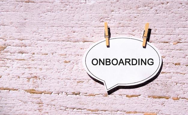 Onboarding su una bolla di discorso bianco con perni di legno