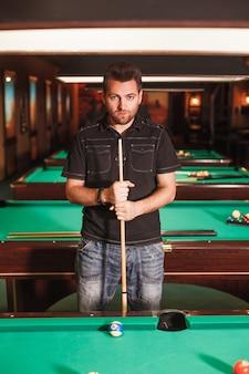 Giocatore concentrato con una stecca in una sala da biliardo.