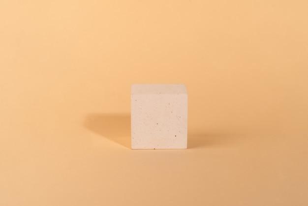 A forma di cubo quadrato oncrete su sfondo beige vetrina per la presentazione del prodotto