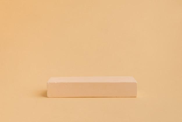 Palcoscenico oncrete di forma rettangolare su sfondo beige vetrina per prodotto