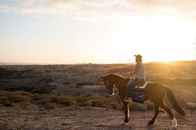 Un uomo solo e isolato che cavalca il suo cavallo la sera con il tramonto sullo sfondo - viaggiando e scoprendo insieme