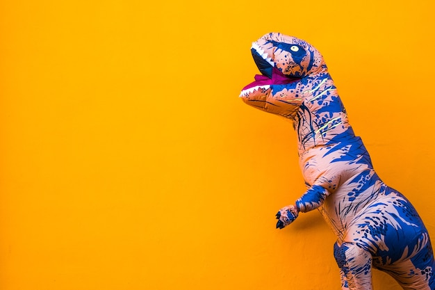 Un dinosauro grande e alto che si diverte e si diverte con lo sfondo arancione - copia e spazio vuoto per scrivere qui il tuo testo