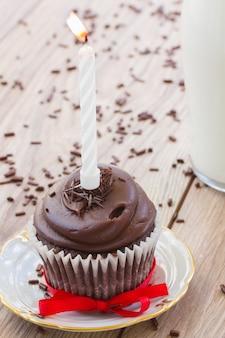 Un bigné di compleanno con candela accesa sul tavolo
