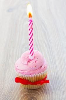 Un compleanno cupcake rosa con candela accesa sul tavolo