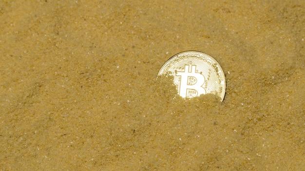 Una moneta cripto bitcoin su sabbia dorata brillante. trovare e minare criptovalute
