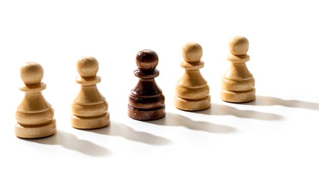 Un pedone degli scacchi nero tra i bianchi. concetto di razzismo e discriminazione.