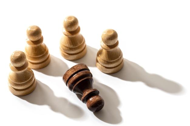 Un pedone di scacchi nero che giace tra i bianchi. concetto di razzismo e discriminazione.