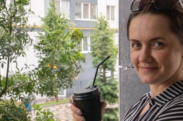 Un bicchiere di carta nero con un coperchio e una cannuccia nelle mani di una giovane donna sorridente felice all'aperto in estate con tempo soleggiato sullo sfondo delle case, in una caffetteria o in un ristorante. caffè da portar via.