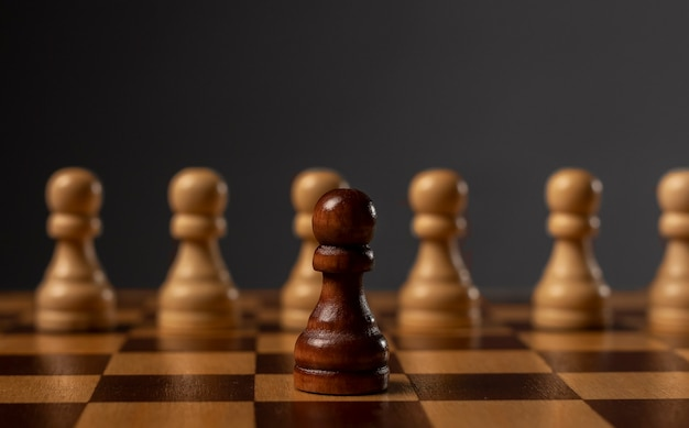 Un pedone nero contro tanti altri. diverso contro il monopolio. concetto di sfida.