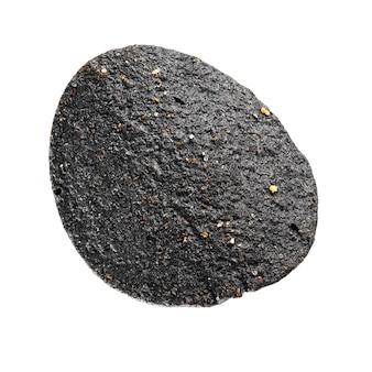 Una patatina nera isolata su fondo bianco. colpo a macroistruzione.