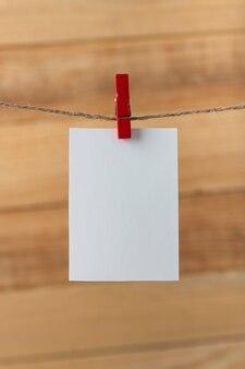 Una carta bianca vuota appesa con la molletta sul piolo della corda. cornice verticale.