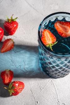 Una tazza di vetro geometrica blu con acqua fresca e frutta fragola con raggi di luce ombreggiati colorati sulla pietra