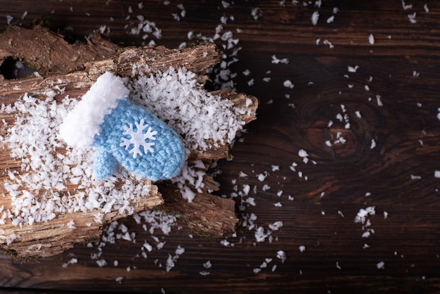 Un guanto blu con un fiocco di neve sulla corteccia e un tavolo di legno scuro nella neve, piatto, da vicino.
