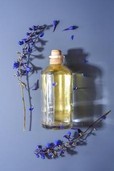 Una bottiglia con olio aromatico cosmetico naturale su una superficie blu nei fiori. piatto lay, concetto di cosmetici biologici naturali per la cura della pelle