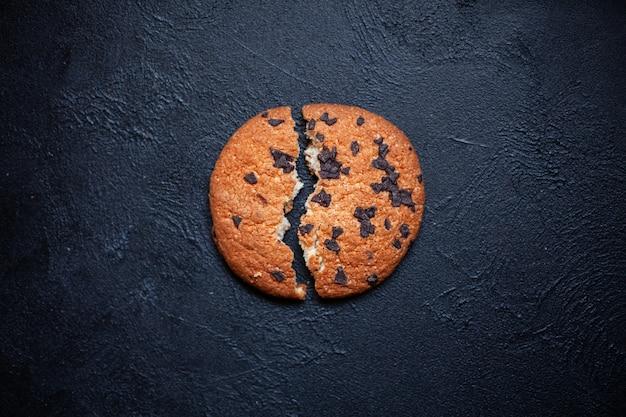 Un biscotto rotto in due pezzi con cioccolato su sfondo nero immagine per un'iscrizione