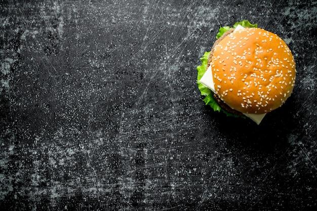 Un hamburger con carne di manzo ed erbe aromatiche. su sfondo nero rustico