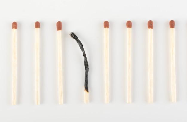Un fiammifero bruciato tra molti incombusti. gruppo di bastoncini o fiammiferi di sicurezza. individualità e concetto di differenza