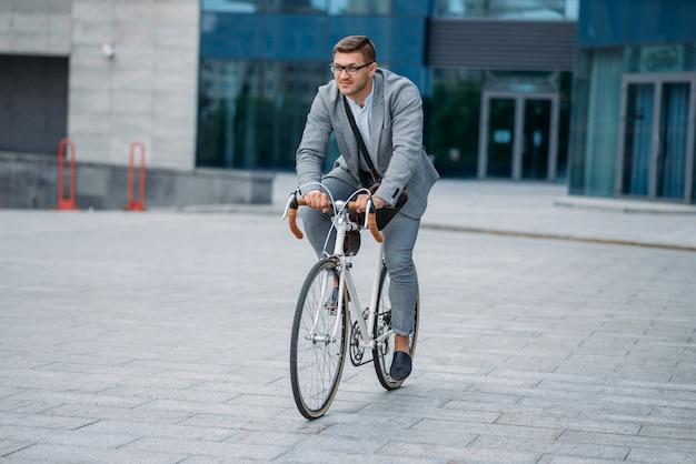 Un uomo d'affari posa in bicicletta presso l'edificio per uffici nel centro cittadino. persona di affari che guida sul trasporto ecologico sulla strada della città