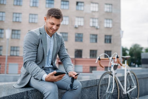 Un uomo d'affari posa con la bicicletta presso l'edificio per uffici nel centro cittadino. persona di affari che guida sul trasporto ecologico sulla strada della città