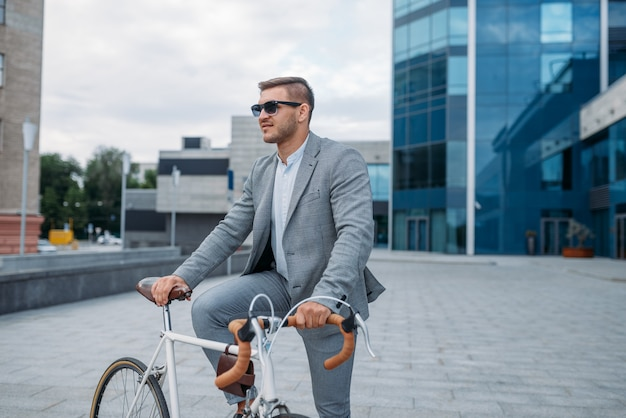 Un uomo d'affari in occhiali da sole posa in bicicletta presso l'edificio per uffici nel centro cittadino. persona di affari che guida sul trasporto ecologico sulla strada della città