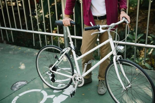 Un uomo caucasico che spinge la sua bicicletta al parco