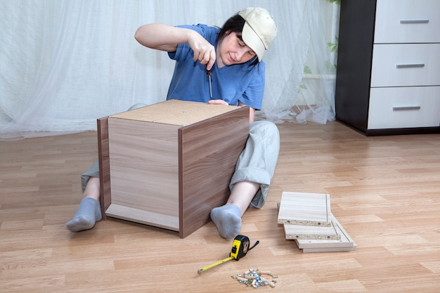 Una donna caucasica che assembla nuovi mobili.