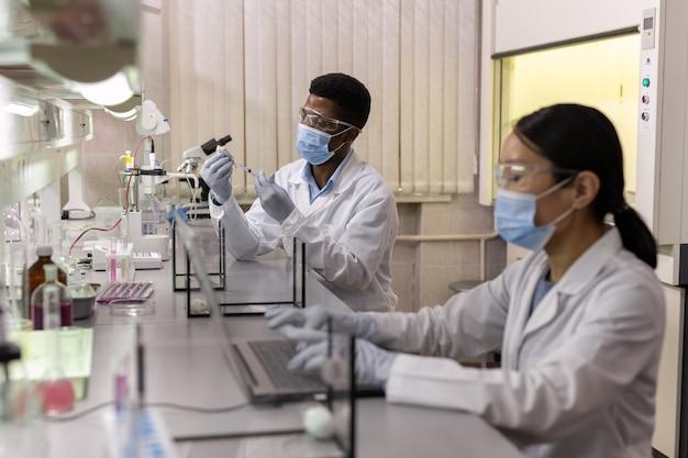 Uno dei chimici con un topo bianco che testa un nuovo vaccino in laboratorio