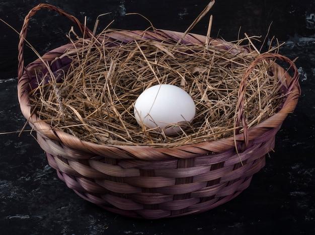 Un uovo di gallina in un cesto con fieno sul nero