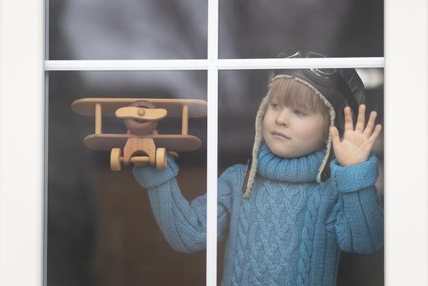 Un bambino che gioca con un aeroplano in legno d'epoca al coperto. kid divertirsi a casa.