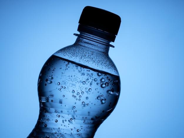 Una bottiglia chiusa di acqua frizzante è isolata su uno sfondo blu
