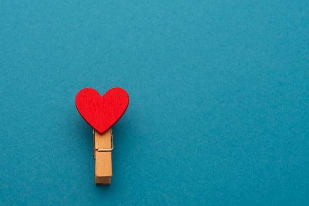 Una molletta da bucato con amore su sfondo blu